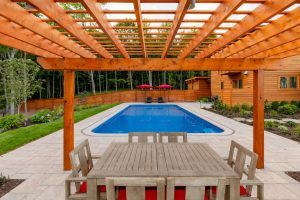 Auburn brown pergola with seating on the side of a beautiful blue pool